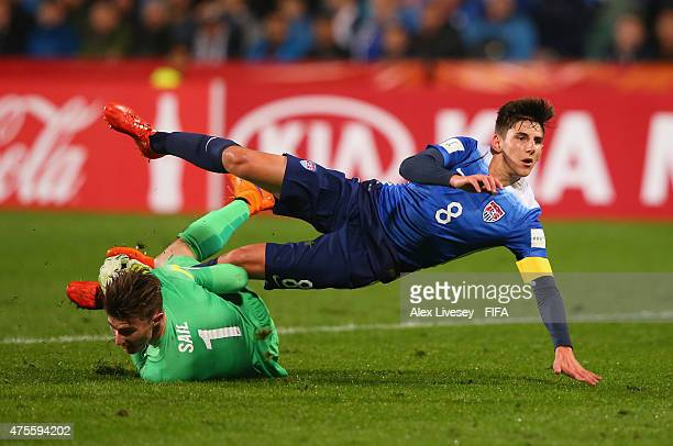 Emerson Hyndman of USA falls over the challenge of Oliver Sail of New Zealand as he scores the second goal during the FIFA U20 World Cup Group A...