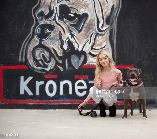 Emery Bingham and Stitch the dog pose with artwork by Toby Lee Jones at Giveback Day at TAP The Artists Projecton May 10 2019 in Los Angeles...