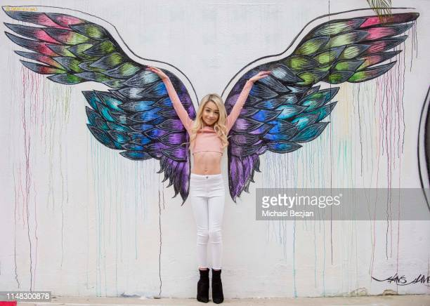 Emery Bingham poses with artwork by Gracie Kim at Giveback Day at TAP The Artists Project on May 10 2019 in Los Angeles California