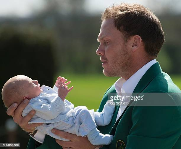 Emglish golfer Danny Willett wearing his Masters champion green jacket holds his newborn son Zachariah James Willett as he poses for a photograph at...