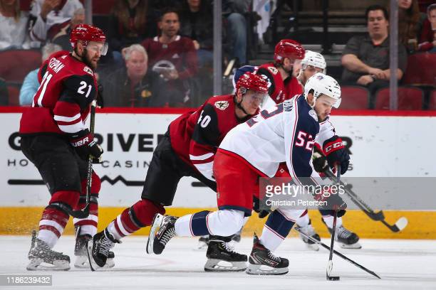 Emil Bemstrom of the Columbus Blue Jackets skates with the puck ahead of Michael Grabner of the Arizona Coyotes during the third period of the NHL...