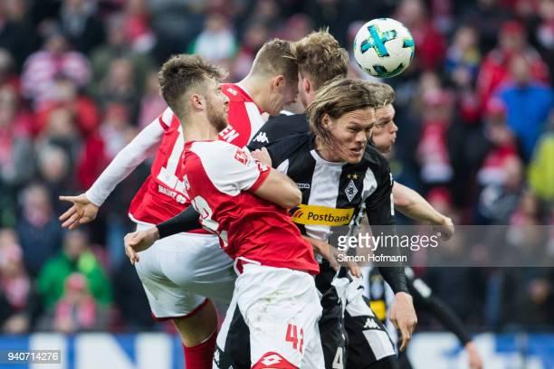 Emil Berggren of Mainz jumps for a header with Nico Elvedi of Moenchengladbach during the Bundesliga match between 1 FSV Mainz 05 and Borussia...
