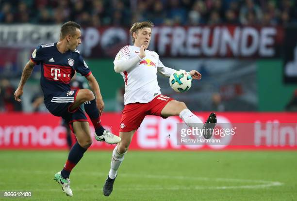 Emil Forsberg of Leipzig and Rafinha of Muenchen vie during the DFB Cup round 2 match between RB Leipzig and Bayern Muenchen at Red Bull Arena on...