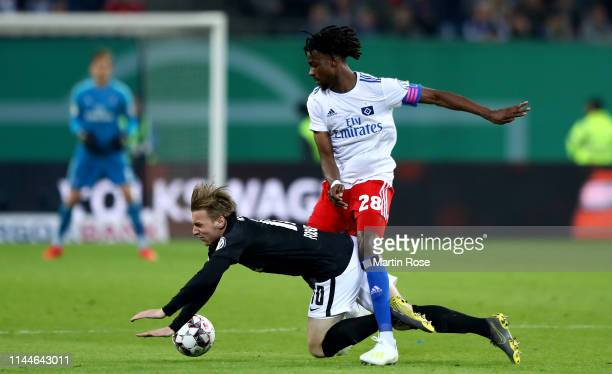 Emil Forsberg of Leipzig is challenged by Gideon Jung of Hamburg during the DFB Cup semi final match between Hamburger SV and RB Leipzig at Imtech...
