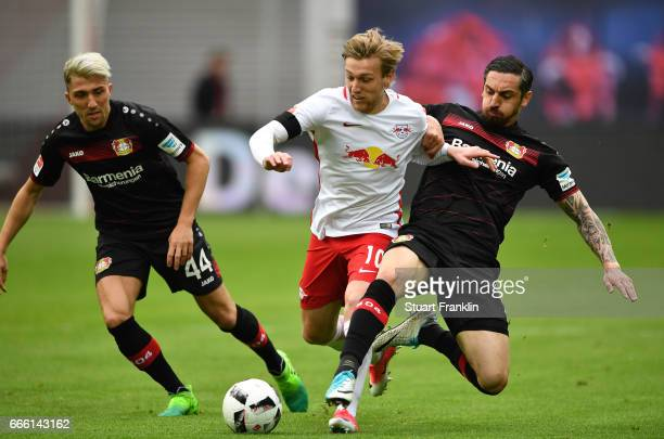 Emil Forsberg of Leipzig is challenged by Kevin Kampl and Roberto Hilbert of Leverkusen during the Bundesliga match between RB Leipzig and Bayer 04...