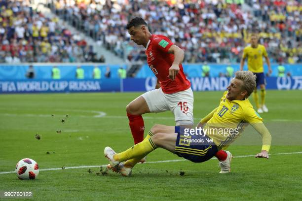 Emil Forsberg of Sweden tackles Blerim Dzemaili of Switzerland during the 2018 FIFA World Cup Russia Round of 16 match between Sweden and Switzerland...