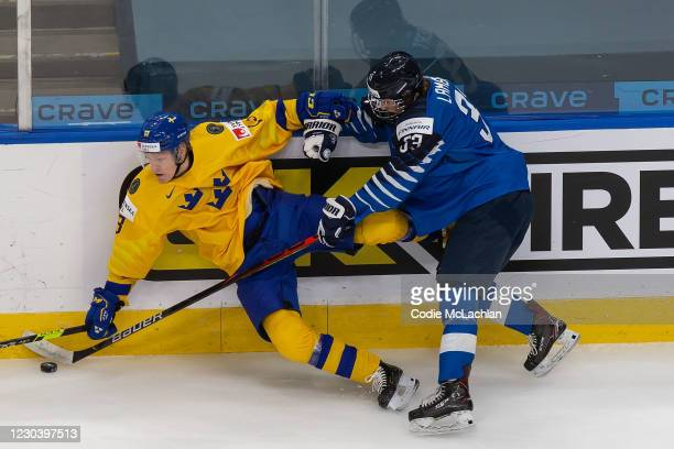 Emil Heineman of Sweden skates against Brad Lambert of Finland during the 2021 IIHF World Junior Championship quarterfinals at Rogers Place on...
