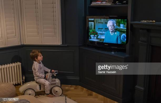 Emil Hussein aged 4 who is the photographer's son watches from home as Queen Elizabeth II addresses the nation in a special broadcast to the United...