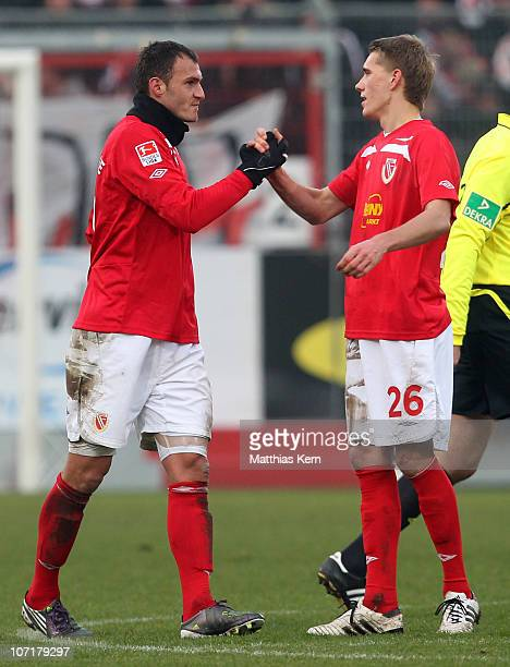 Emil Jula of Cottbus and team mate Nils Petersen shake hands after the Second Bundesliga match between FC Energie Cottbus and Erzgebirge Aue at...