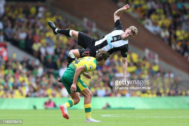 Emil Krafth of Newcastle comes crashing down to the ground after colliding with Todd Cantwell of Norwich during the Premier League match between...