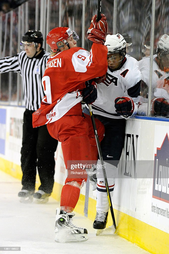 Emil Kristensen #9 of Team Denmark body checks Emerson Etem #10 of Team USA during the 2012 World Junior Hockey Championship game at Rexall Place on December 26, 2011 in Edmonton, Alberta, Canada. Team USA defeated Team Denmark 11-3.