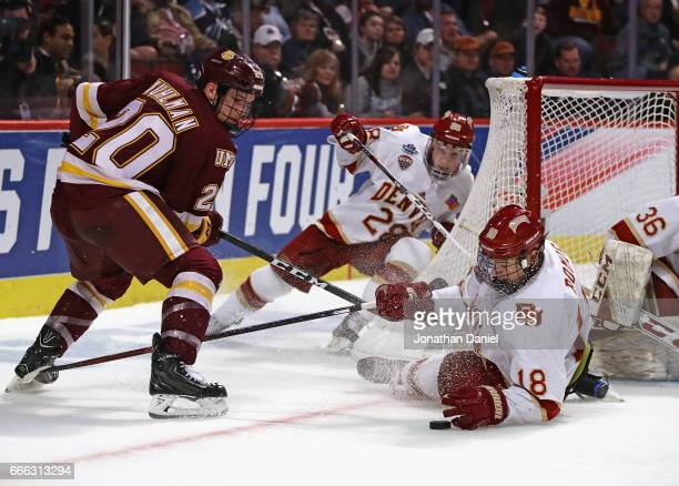 Emil Romig of the Denver Pioneers drops to the ice to block a shot by Karson Kuhlman of the Minnesota-Duluth Bulldogs during the 2017 NCAA Division I...