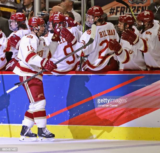Emil Romig of the Denver Pioneers is congratulated by teammates after scoring a goal in the first period against the Notre Dame Fighting Irish during...