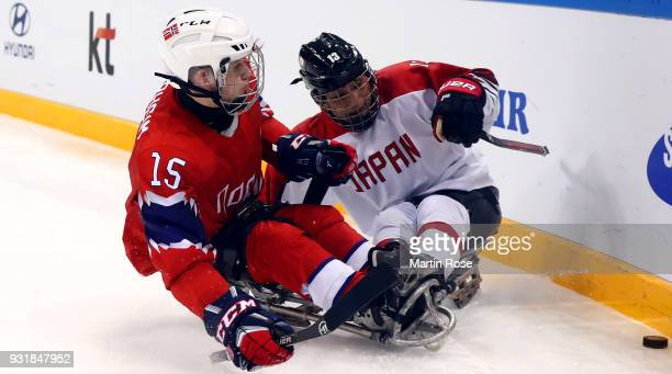 Emil Sorheim of Norway battles for the puck with Mamoru Yoshikawa of Japan in the Ice Hockey Classification game between Norway and Japan during day...