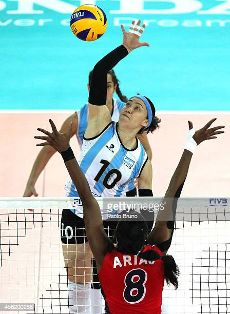 Emilce Sosa of Argentina spikes the ball as Perez Arias of Dominican Republic blocks during the FIVB Women's World Championship pool A match between...