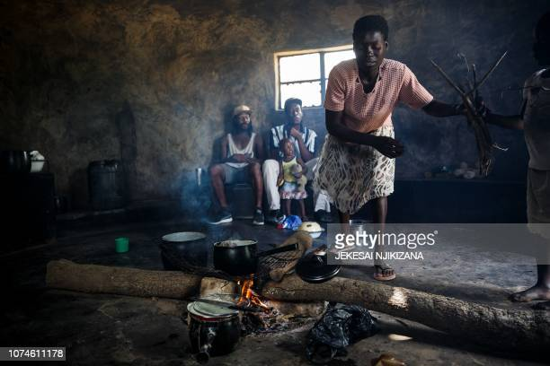 Emilda Chingarambe stokes her kitchen stove with firewood as she prepares a meal next to her family on December 10 in Chinamhora district northeast...