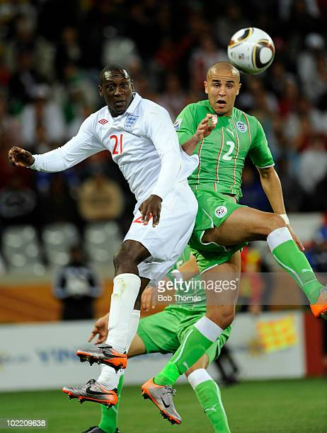 Emile Heskey heads the ball with Madjid Bougherra of Algeria during the 2010 FIFA World Cup South Africa Group C match between England and Algeria at...