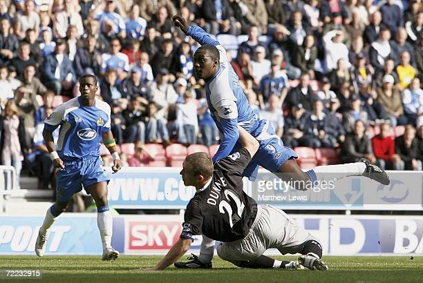Emile Heskey of Wigan beats Richard Dunne of Manchester to score a goal during the Barclays Premiership match between Wigan Athletic and Manchester...