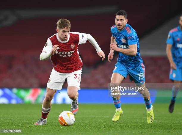 Emile Smith Rowe of Arsenal breaks past Giorgos Masouras of Olympiacos during the UEFA Europa League Round of 16 Second Leg match between Arsenal and...