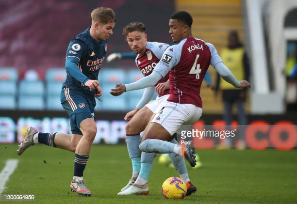 Emile Smith Rowe of Arsenal is challenged by Matthew Cash of Aston Villa and Ezri Konsa of Aston Villa during the Premier League match between Aston...