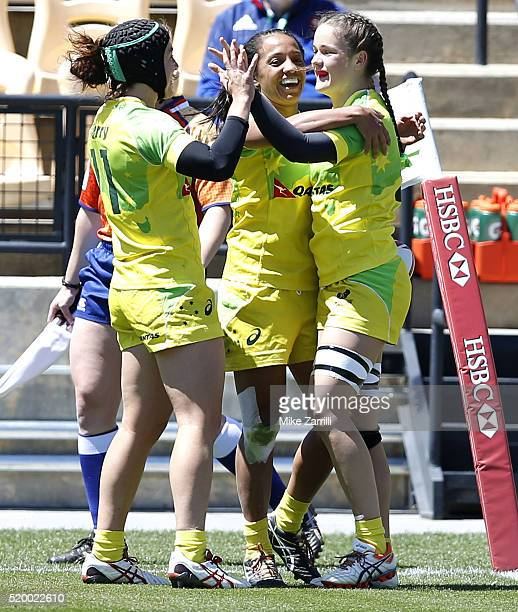 Emilee Cherry and Amy Turner of Australia congratulate teammate Charlotte Caslick after her score during the match against the United States at Fifth...