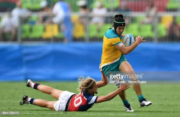 Emilee Cherry of Australia makes a break past Richelle Stephens of the United States during the Women's Rugby Sevens Pool A match between Australia...