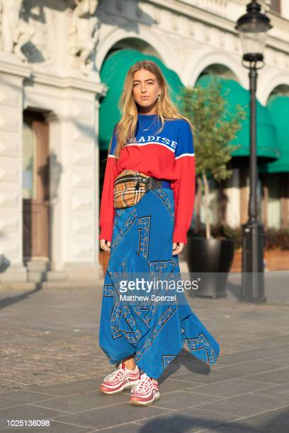 Emili Sindlev is seen on the street during Fashion Week Stockholm SS19 wearing red/blue sweater with blue pattern skirt plaid hip belt bag and pink...