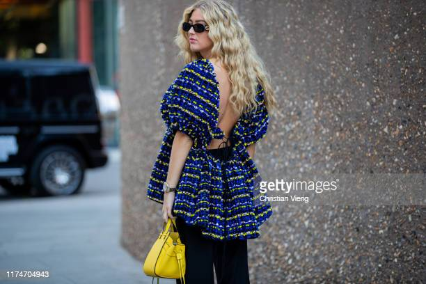 Emili Sindlev is seen wearing navy backless top, yellow Loewe bag, black pants outside Ports 1961 during London Fashion Week September 2019 on...