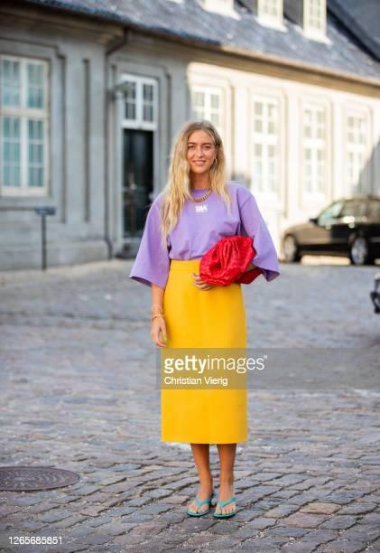 Emili Sindlev is seen wearing yellow skirt, purple tshirt, red Bottega Veneta bag, sand outside Selected during Copenhagen Fashion Week Spring/Summer...