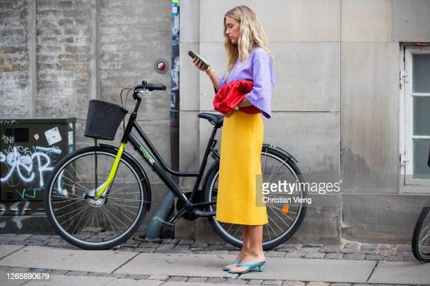Emili Sindlev is seen wearing yellow skirt, purple tshirt, red Bottega Veneta bag, sandals outside Selected during Copenhagen Fashion Week...