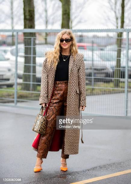 Emili Sindlev seen wearing coat with print, Balenciaga bag with animal print, python snake print pants outside Lala Berlin during Copenhagen Fashion...