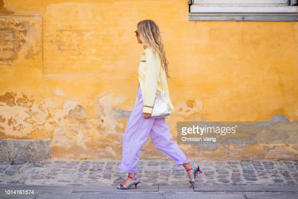 Emili Sindlev weairng purple pants, yellow jacket is seen outside Lovechild 1979 during the Copenhagen Fashion Week Spring/Summer 2019 on August 9,...