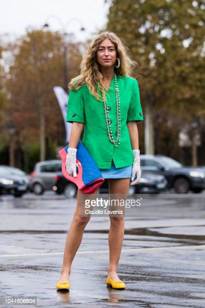 Emili Sindlev wearing a green shirt light blue skirt yellow shoes blue and red Chanel bag and white lace gloves is seen before the Chanel show on...