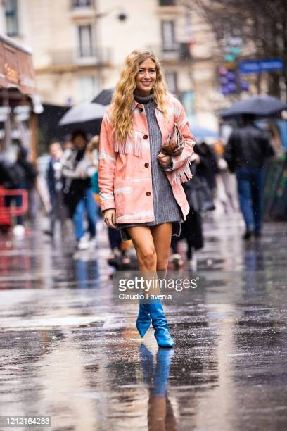 Emili Sindlev, wearing a grey knitted dress, prink fringed jacket and blue boots, is seen outside Sacai, during Paris Fashion Week - Womenswear...