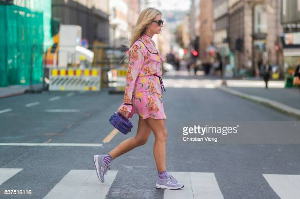 Emili Sindlev wearing a pink dress with floral print sneakers striped socks outside Moods of Norway on August 22 2017 in Oslo Norway