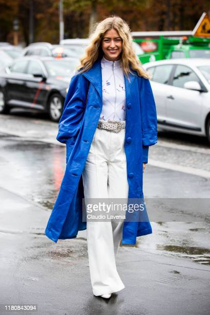Emili Sindlev, wearing a white printed top, white pants, blue coat and red bag, is seen outside the Chanel show during Paris Fashion Week -...