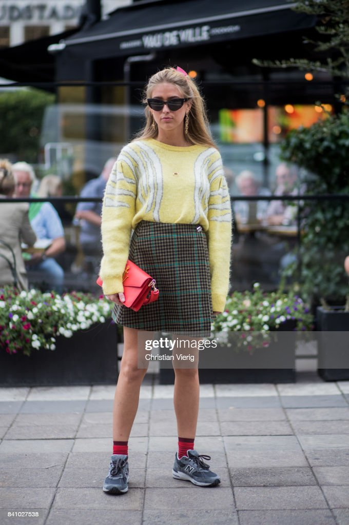 Emili Sindlev wearing a yellow sweater, skirt red JW Anderson bag outside Rodebjer on August 30, 2017 in Stockholm, Sweden.