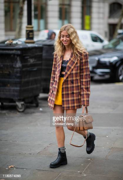 Emili Sindlev wearing brown Chanel bag cropped top mini skirt plaid blazer is seen outside Erdem during London Fashion Week February 2019 on February...