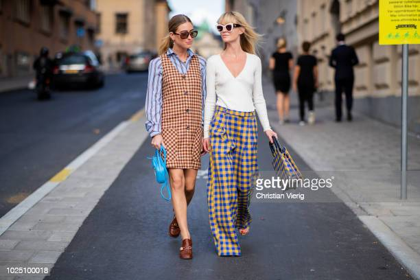 Emili Sindlev wearing brown sleeveless checked dress, striped button shirt, blue Balenciaga bag with animals printed, leather shoes and Jeannette...