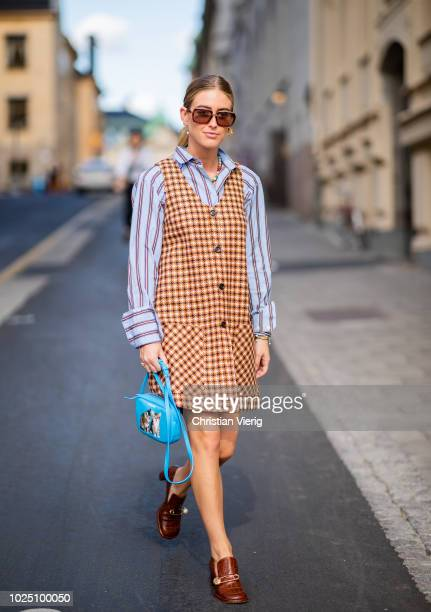 Emili Sindlev wearing brown sleeveless checked dress striped button shirt blue Balenciaga bag with animals printed leather shoes seen during...