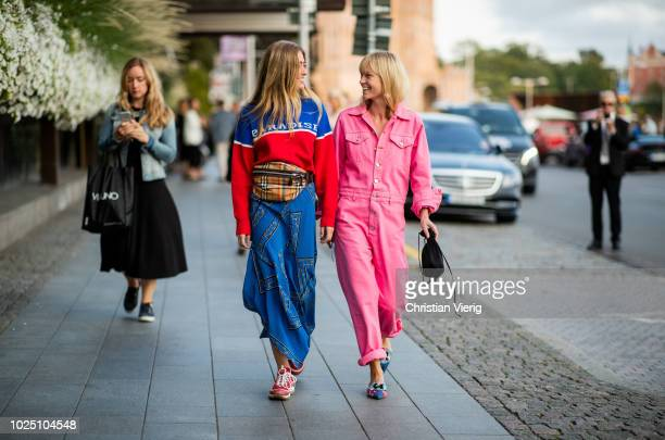 Emili Sindlev wearing Burberry fanny bag blue red sweater with print Paradise blue skirt and Jeannette Madsen wearing pink overall is seen during...