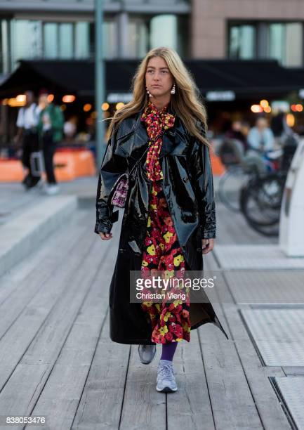 Emili Sindlev wearing dress with floral print black rain coat outside Mayow on August 23 2017 in Oslo Norway