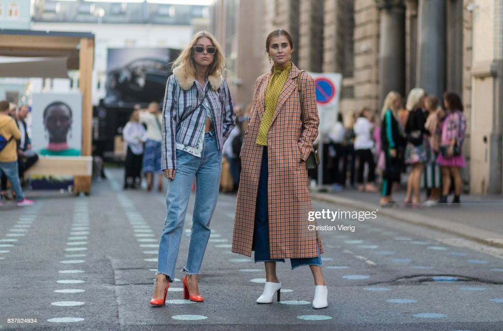 Emili Sindlev wearing jacket with collar, cropped denim jeans and Darja Barannik wearing a plaid coat, yellow button shirt, white boots, cropped denim jeans outside Line of Oslo on August 22, 2017 in Oslo, Norway.