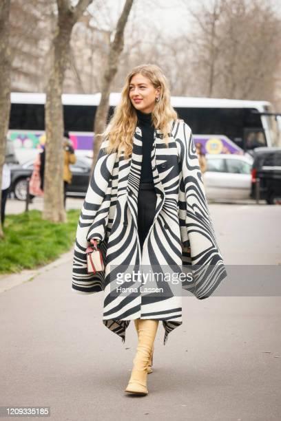 Emili Sindlev wearing Loewe oversized poncho, beige knee high boots, burgundy mini bag outside the Loewe show during the Paris Fashion Week...