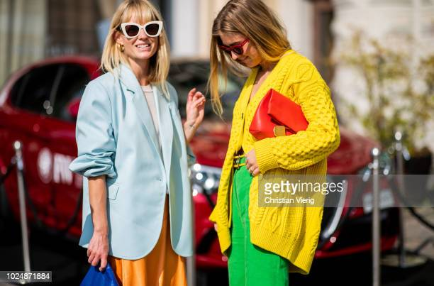 Emili Sindlev wearing yellow knit cardigan green wide leg pants Burberry clutch and Jeannette Madsen wearing orange midi skirt ankle boots light blue...