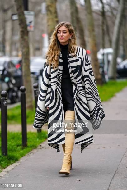 Emili Sindlev wears a black and white zebra pattern printed poncho long coat, a black turtleneck dress, beige leather thigh high boots, earrings,...