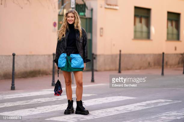 Emili Sindlev wears a black jacket a black turtleneck pullover green skirt with large blue pockets a bag with red printed flames black leather boots...