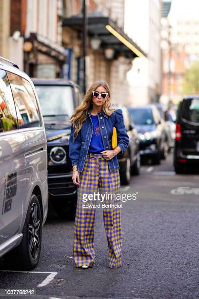 Emili Sindlev wears a blue denim skirt a blue top yellow and blue checked flare pants a yellow clutch during London Fashion Week September 2018 on...