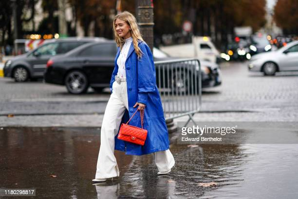 Emili Sindlev wears a blue long coat, a white top, a belt, a red quilted Chanel bag, white flared pants, outside Chanel, during Paris Fashion Week -...
