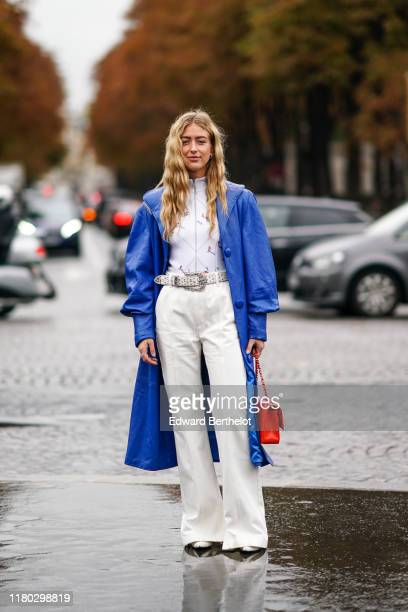 Emili Sindlev wears a blue long coat a white top a belt a red quilted Chanel bag white flared pants outside Chanel during Paris Fashion Week...